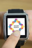 picture of wrist  - Businesswoman with smart watch on wrist against autism awareness month - JPG
