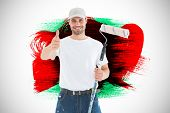 picture of gesture  - Happy man with paint roller gesturing thumbs up against green red and black paint - JPG