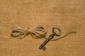 stock photo of hasp  - Vintage key and a coil of rope on the old cloth  - JPG