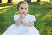 foto of teething baby  - Cute happy little baby girl in white dress scratching first teeth in park on green grass - JPG