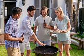 picture of braai  - group of friends having outdoor garden barbecue with alcoholic beer drinks - JPG
