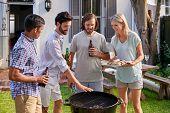 stock photo of braai  - group of friends having outdoor garden barbecue with alcoholic beer drinks - JPG