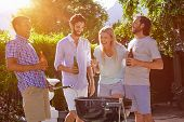 image of braai  - group of friends having outdoor garden barbecue laughing with alcoholic beer drinks - JPG