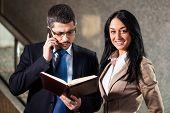 stock photo of people talking phone  - Business people standing in lobby - JPG