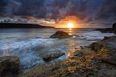 pic of horizon  - The sun rising over the horizon at Long Bay Malabar its sun rays underlighting the edges of the clouds and highlighting the foreground rocks in warm light - JPG