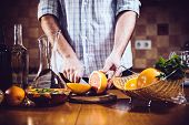 picture of sangria  - Man cuts fresh grapefruits for making sangria for home party - JPG