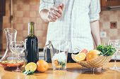 image of sangria  - The man squeezes grapefruit juice in a decanter for making home sangria for home party - JPG