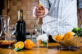 stock photo of sangria  - The man squeezes grapefruit juice in a decanter for making home sangria for home party - JPG