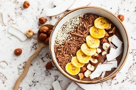 stock photo of seed  - Chocolate hazelnut smoothie bowl topped with sliced banana - JPG