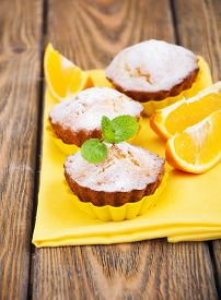foto of bakeshop  - Homemade Muffins Ready for Breakfast with orange slices on a napkin on wooden background - JPG