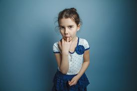 pic of finger-licking  - a girl of seven European appearance brunette stuck a finger in his mouth on a gray background - JPG