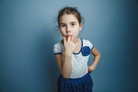 foto of finger-licking  - a girl of seven European appearance brunette stuck his index finger in his mouth on a gray background - JPG