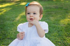image of teething baby  - Cute happy little baby girl in white dress scratching first teeth in park on green grass - JPG