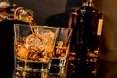 Постер, плакат: Barman Pouring Whiskey In Front Of Whiskey Glass And Bottles