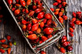 picture of wild-brier  - Rosehips in a wicker metal basket on a wooden surface - JPG