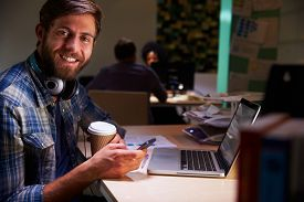 image of late 20s  - Office Worker With Coffee At Desk Working Late On Laptop - JPG