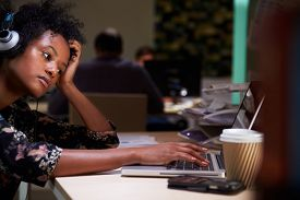 pic of late 20s  - Female Office Worker With Coffee At Desk Working Late - JPG