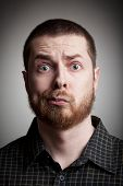 Face of funny amazed guy isolated on gray background