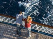 Young honeymoon couple on the stern of a cruise ship.