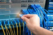 man working in network server room with fiber optic hub for digital communications and internet poster