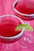 pink cocktails in salt rimmed glasses with lime wedge - narrow DOF
