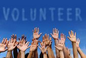 stock photo of hand gesture  - volunteer group raising hands against blue sky background - JPG
