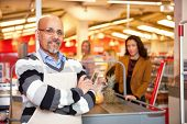 stock photo of grocery store  - Portrait of a grocery store cashier standing at a checkout counter - JPG