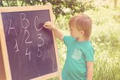 Cute Little Boy Writing Letters And Numbers At Blackboard In The Garden. Toned. poster