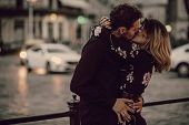 Stylish Gypsy Couple In Love Kissing In Evening City Street At Moving Car Lights. Woman And Man Embr poster