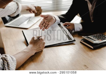 poster of Hand Of Young Man Customer Signing Contract For Buying House With Real Estate Broker In Suit At Esta