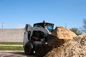 stock photo of dozer  - A bobcat doing some construction work with sand - JPG