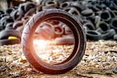Old Worn And Dirty Car Tire. Small Dirty Old Tire And Used Tires Pile In Dump At Background poster