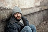 Poor Homeless Man Sitting Near Wall On Street. Space For Text poster