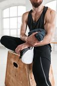 Close Up View On Strong Male Athlete Resting On Wooden Box After Cross Intense In Workout Gym. Fit P poster