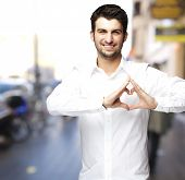 portrait of a young man doing a heart symbol against a street background