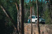 Man Standing On Rock Cliff Near White Suv Car With View On Lake. View Through Trees. Adventure Conce poster