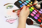 foto of makeup artist  - Makeup artist is sketching makeup style on a paper - JPG