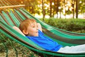 Happy Child Relaxing In Hammock. Summer Vacation Concept. Cute Boy Lying In A Hammock In Garden, Dre poster