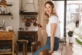 Portrait of european blond woman 20s wearing casual t-shirt using smartphone while standing in styli poster