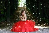 Beautiful woman in a red dress walking in alleyway in park