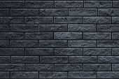 Texture Of Dark Gray Brick Wall. The Wall Is Tiled Decorative. Dark Stone Background Of House Facade poster