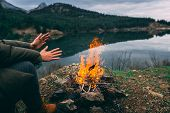 Hands Of Young Woman Warming Up By Camp Fire. Body Parts Of Adult Female At Nature. Camping. Fire. poster