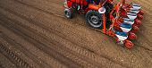 Aerial View Of Tractor With Mounted Seeder Performing Direct Seeding Of Crops On Plowed Agricultural poster