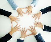 Vista superior dos empresários segurando as mãos juntas sobre uma superfície branca
