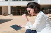 Pensive Female Writer Thinking Over Article Outdoors. Side View Of Woman In Sunglasses Sitting Near  poster
