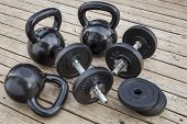 exercise weights - kettlebells and dumbbells on a wooden deck - a home gym concept