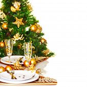 Photo of Christmastime table setting border, beautiful decorated Christmas tree isolated on white background, romantic holiday dinner, luxury white dishware decorated with golden ribbon