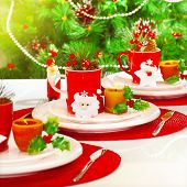 Photo of beautiful Christmas table setting, New Year banquet, adorned evergreen tree, warm yellow su