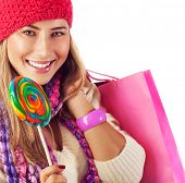 Image of nice blond girl wearing warm winter red hat and eating tasty sugar candy, sweets shop, Chri