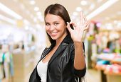 Portrait Of Cheerful Young Woman Gesturing Okay Sign at a mall
